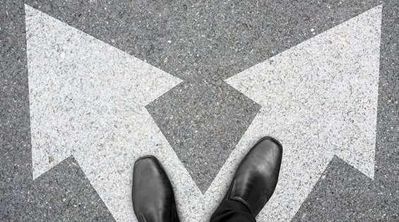 Black Shoes Standing on Decision Arrows